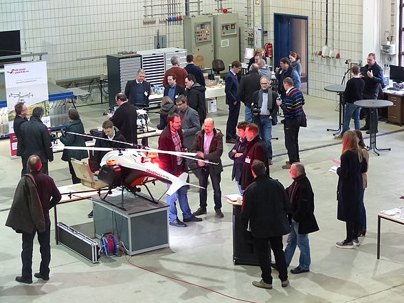 unmanned aerial vehicles in an exhibition hall, surrounded by workshop participants